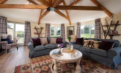 The charming sitting room is a convivial space for families and groups to sit and relax together or play board games in front of the cosy wood burning stove.