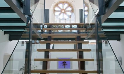 The bespoke glass and oak staircase is a statement piece framed by an ornate rose-glass window.