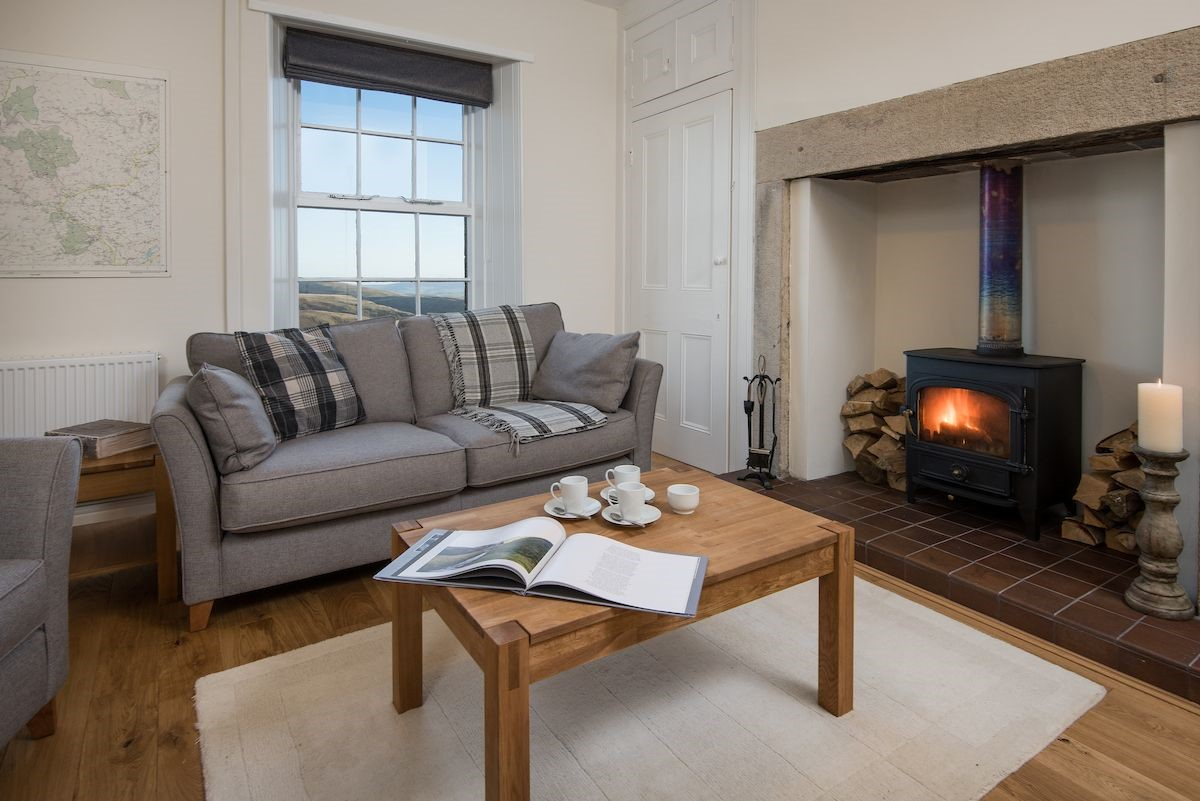 The sitting room provides an inviting combination of cosy wood burner and big sky views.
