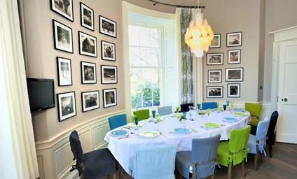Groups tend to gather in the delightful kitchen-dining room. Here, double height windows and original artworks add a dramatic flair.