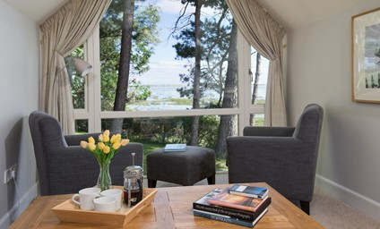 The stunning sitting room with large feature window where you can sink into the comfort of an armchair and enjoy the spirit-lifting views over the bay.