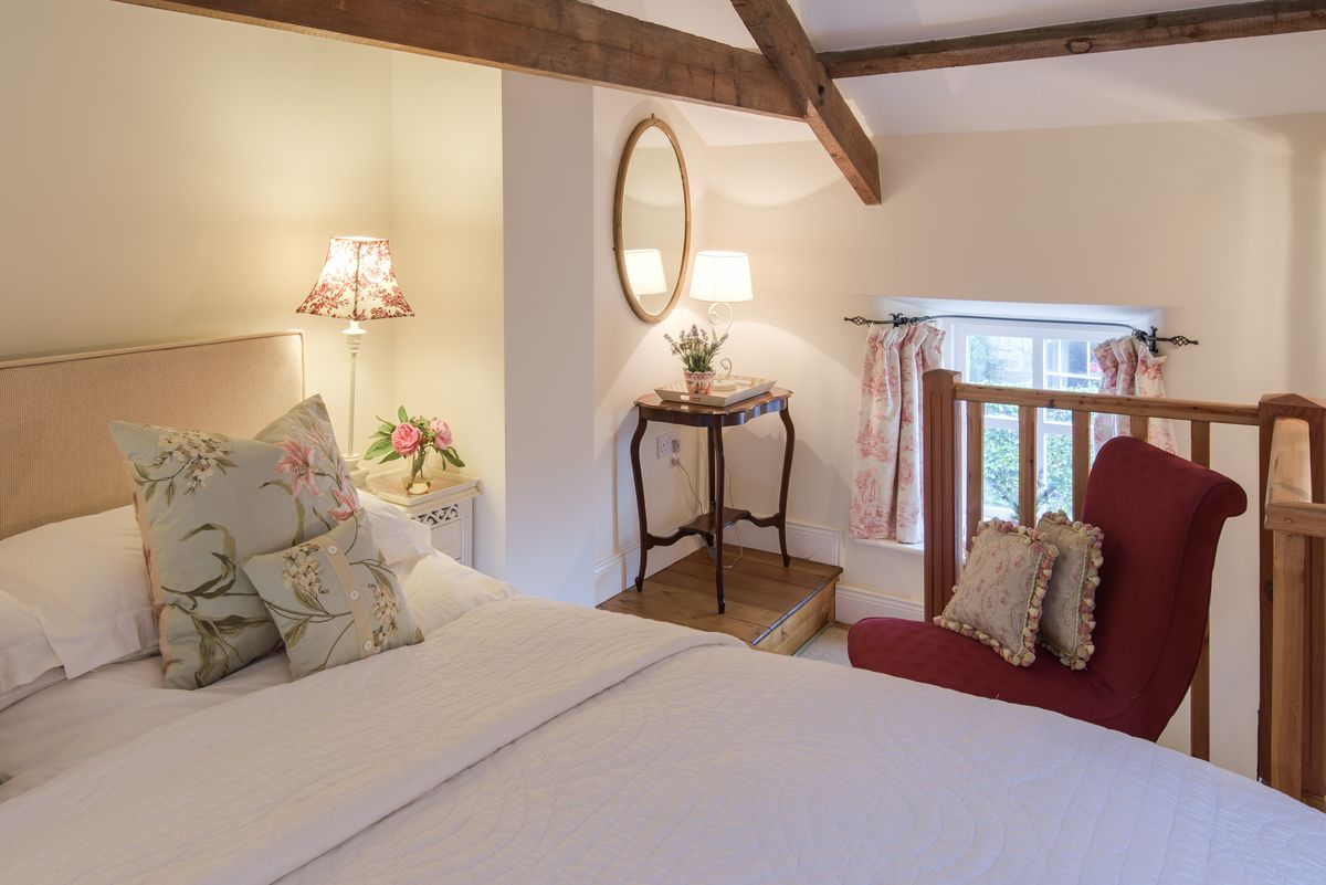 A mezzanine level bedroom with wooden beams and pretty decor in a country cottage in Northumberland.