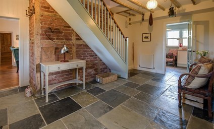 The welcoming hallway with original oak beams, exposed brickwork, reclaimed church pews and characterful touches.