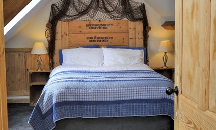 A unique headboard draped with original fishing nets are a gentle reminder of the history of the property.