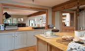 Heiton Mill House - kitchen with window looking through to open plan living area