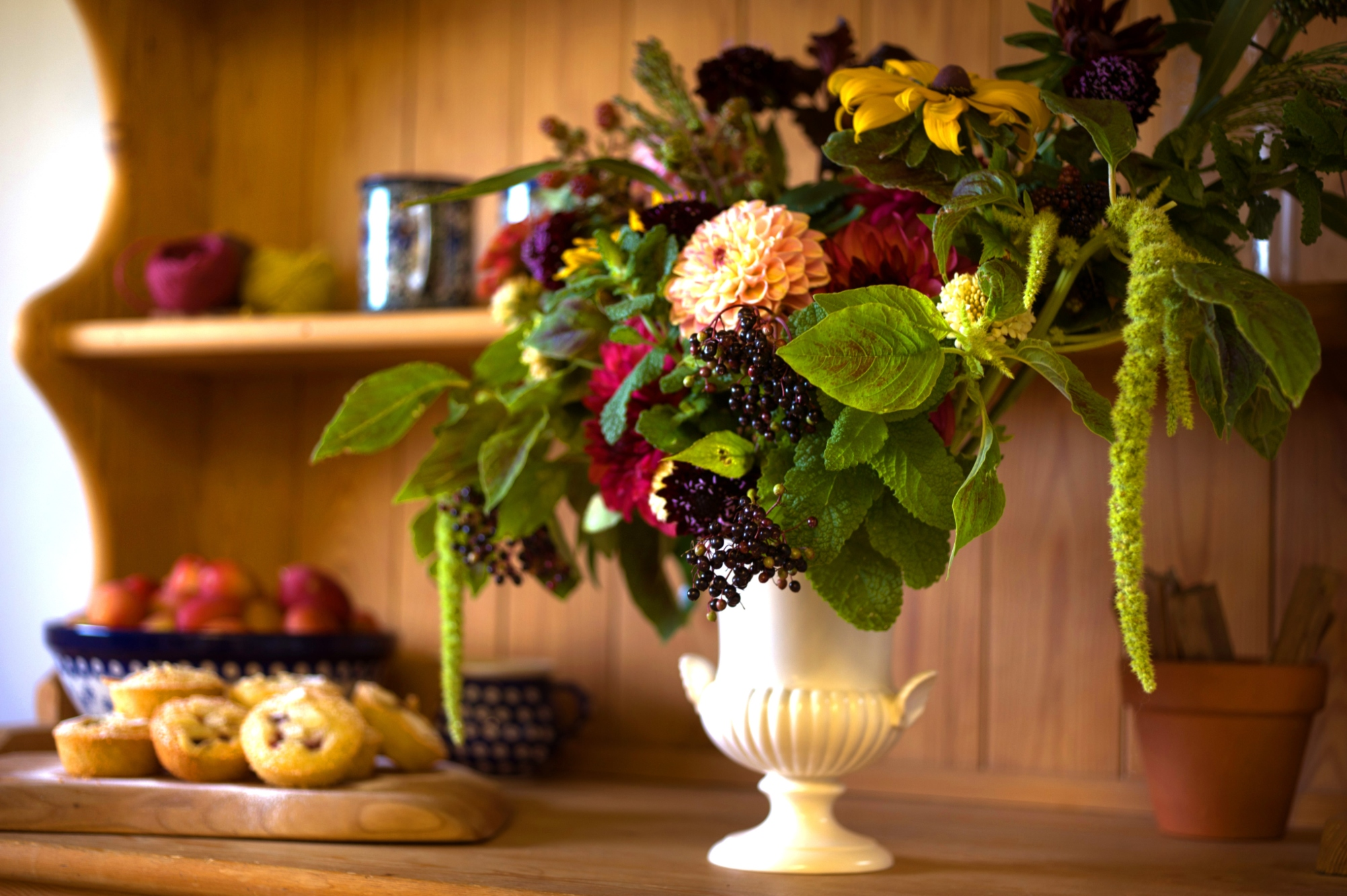 A floral display in a white vase. Try flower arranging on holiday with Crabtree & Crabtree in Northumberland.